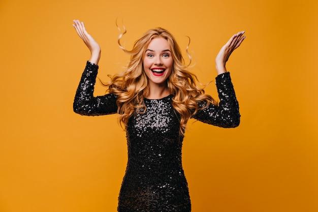 Ragazza meravigliosa emozionante che posa sulla parete gialla. emotiva donna formosa in abito nero che esprime eccitazione.