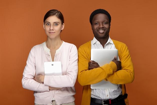 Stagista maschio afroamericano giovane eccitato e il suo collega femminile carino attraente in posa uno accanto all'altro con tavoletta digitale e laptop, pronto per il loro primo giorno lavorativo, sorridendo felicemente