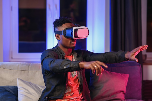 Excited young african-american man extending hand forward, using virtual reality headset sitting on bed, copy space