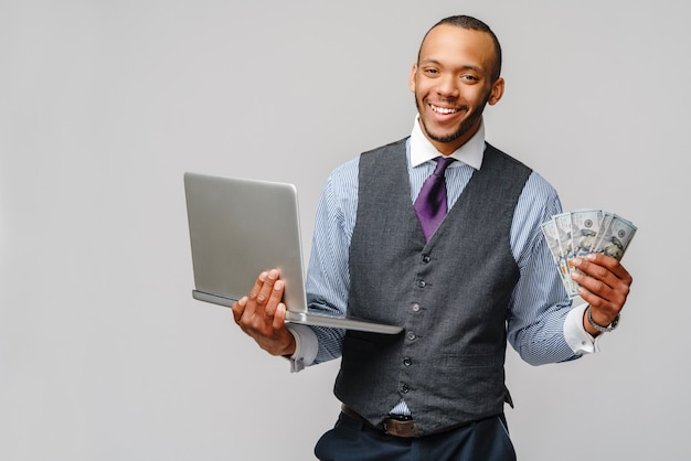 明るい灰色の壁に現金とラップトップを保持している興奮している若いアフリカ系アメリカ人