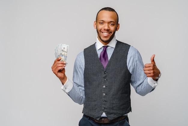 現金お金を押しながら明るい灰色の壁に親指を現して興奮している若いアフリカ系アメリカ人