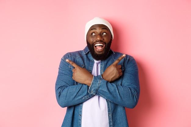 興奮した若いアフリカ系アメリカ人の男は、横向き、2つの選択肢を示し、決定を下し、幸せそうに笑って、ピンクの背景の上に立っています