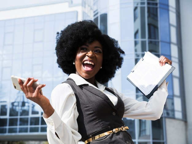 Excited young african businesswoman holding mobile phone and clipboard