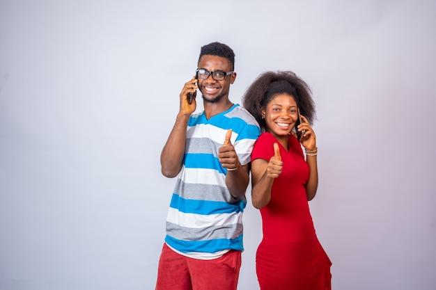 Взволнованные молодые африканцы делают телефонные звонки, стоя на белом, поднимают палец вверх