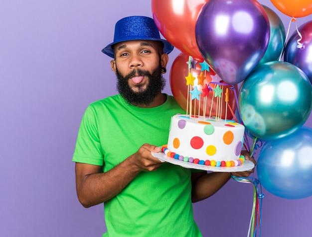 Eccitato giovane ragazzo afro-americano che indossa un cappello da festa che tiene palloncini con una torta che mostra la lingua isolata sulla parete blu
