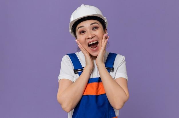 Возбужденная молодая азиатская девушка-строитель с белым защитным шлемом кладет руки на лицо и смотрит вперед