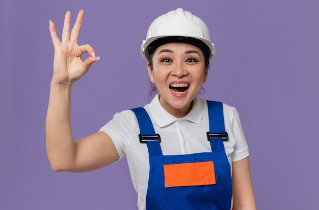 Okサインを身振りで示す白い安全ヘルメットを持つ興奮した若いアジアのビルダーの女性