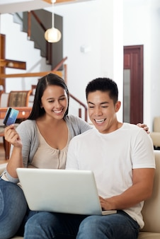 Возбужденные молодые азиатские пары, сидя на диване у себя дома с ноутбуком и кредитной картой