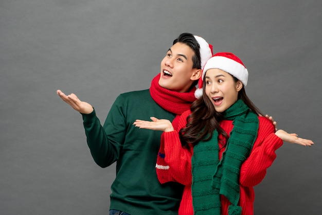 Excited young asian couple wearing christmas theme clothes with open palms