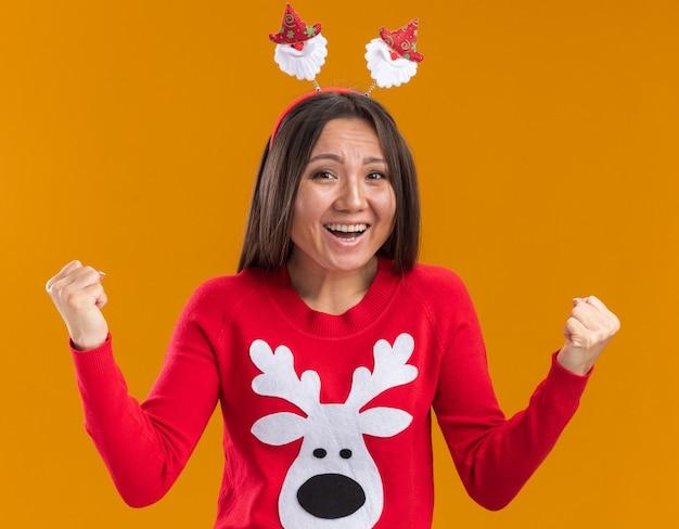 Возбужденная молодая азиатская девушка в рождественском обруче для волос со свитером, показывающим жест да, изолирована на оранжевой стене