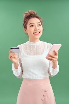 Возбужденная молодая азиатская дама изолирована на зеленом фоне с помощью мобильного телефона, держащего кредитную карту.