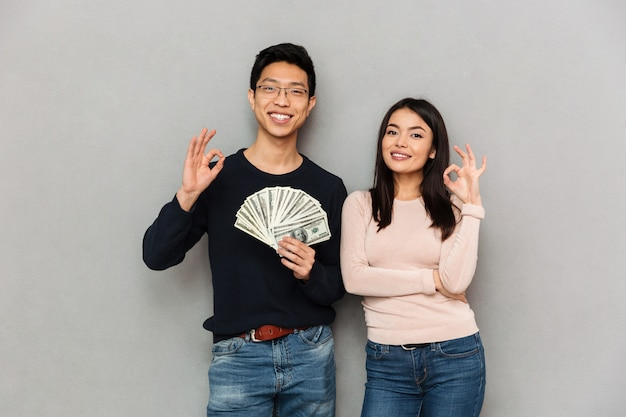 Excited young asian loving couple holding money showing okay gesture.