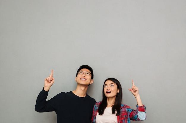 興奮して若いアジア愛するカップルを指しています。