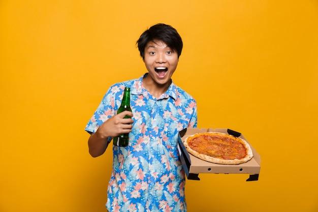 興奮した若いアジア人男性がピザを飲みながら黄色のスペースに孤立して立っています。