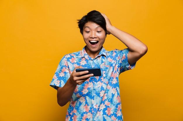휴대 전화로 노란색 공간 플레이 게임에 고립 된 서 흥분된 젊은 아시아 남자.