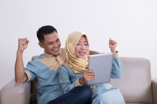 Excited young asian muslim family raised arm