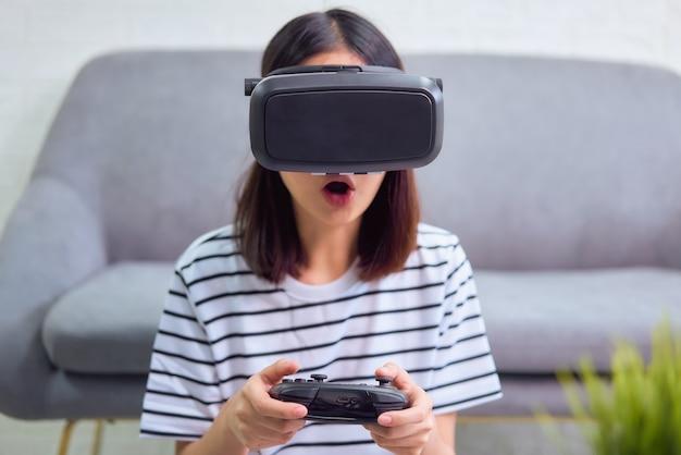 Возбужденная молодая азиатская женщина с помощью гарнитуры виртуальной реальности и джойстиков, концепции связи и интерфейсов цифровых технологий.