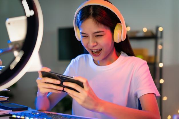 헤드셋을 끼고 스마트폰으로 온라인 게임을 하고 인터넷 라이브 방송을 하는 흥분된 젊은 아시아 여성.