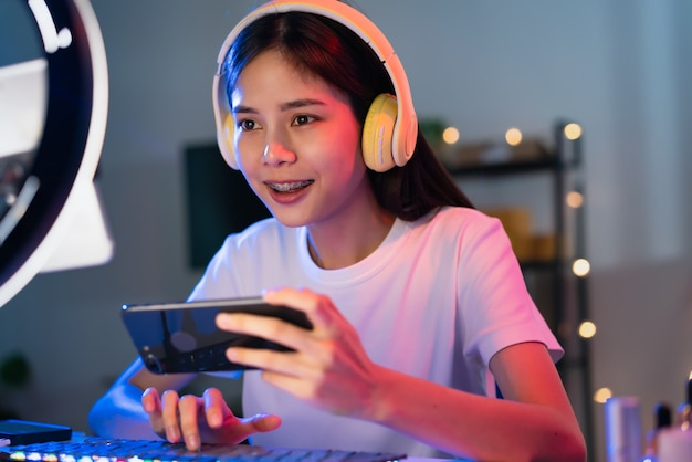 Excited young asian woman wearing headset and playing online game on smartphone with live broadcasting on internet