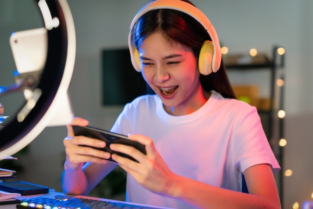 Excited young asian woman wearing headset and playing online game on smartphone with live broadcasting on internet.