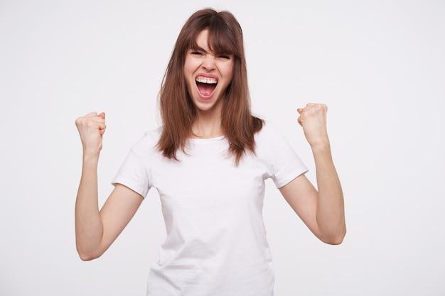 Возбужденная молодая привлекательная шатенка в простой белой футболке радостно кричит и эмоционально поднимает кулаки, радуясь чему-то, стоя у белой стены