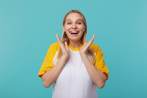 青い背景の上にポーズをとっている間白と黄色のtシャツを着て、カメラを喜んで見ながら感情的に彼女の手のひらを上げる興奮した若い魅力的な長い髪のブロンドの女性