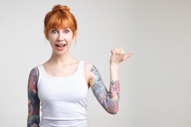 Возбужденная молодая привлекательная рыжая татуированная женщина удивленно округляет глаза, показывая в сторону с поднятой рукой, изолирована на белом фоне в повседневной рубашке