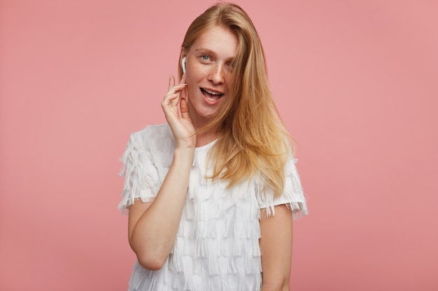 Excited young attractive redhead woman with casual hairstyle holding raised hand on earpiece and looking joyfully at camera with wide mouth opened, isolated over pink background
