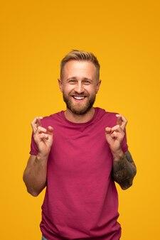 행운을 빌어 손가락을 유지하고 노란색에 대한 행복한 미소로 카메라를보고 캐주얼 셔츠에 흥분된 젊은 수염 난 남성