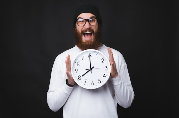 An excited young and bearded man is holding a big white clock on black background.