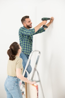 Excited young bearded man standing on ladder and turning screw into wall while hanging picture on wall with wife