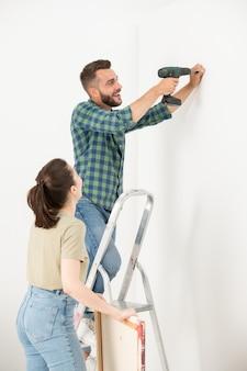 はしごの上に立って、妻と一緒に壁に絵を掛けながらネジを壁に回す興奮した若いひげを生やした男