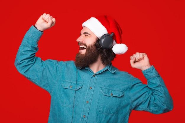 クリスマスの帽子をかぶった興奮した若いひげを生やした男は、ヘッドフォンとダンスで音楽を聴いています。