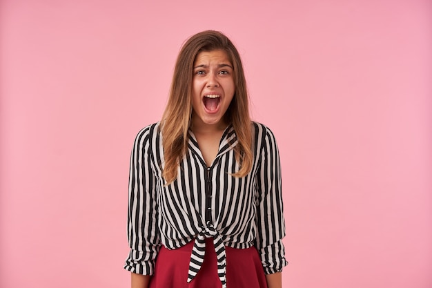 Eccitato giovane bella donna dai capelli castani con trucco naturale aggrottando la fronte mentre urla disperatamente, vestito con abiti festivi mentre posa sul rosa