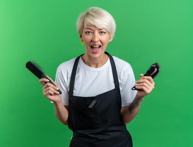 Возбужденная молодая красивая женщина-парикмахер в униформе держит машинку для стрижки волос с расческой, изолированной на зеленой стене