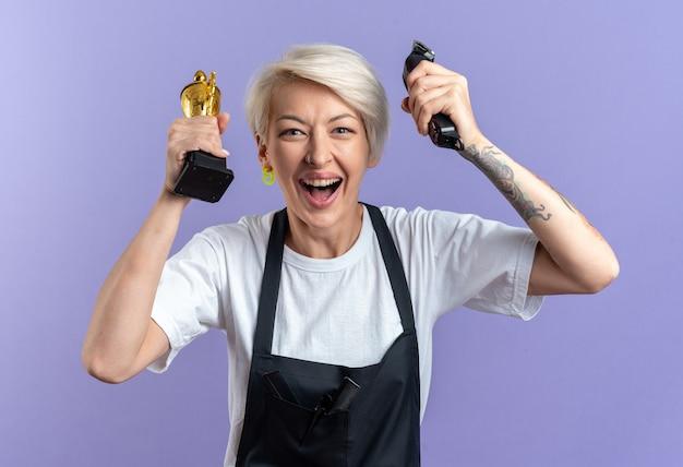 Возбужденная молодая красивая женщина-парикмахер в униформе держит кубок победителя с машинками для стрижки волос, изолированными на синей стене