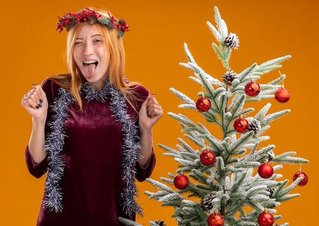 赤いドレスと花輪を身に着けているクリスマスツリーの近くに立っている興奮した若い美しい少女は、舌を示し、オレンジ色の壁に分離されたイエスのジェスチャーをしています