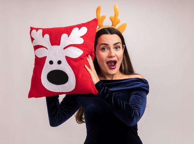 青いドレスと白い背景で隔離の顔の周りにクリスマス枕を保持しているクリスマスの髪のフープを身に着けている興奮した若い美しい少女