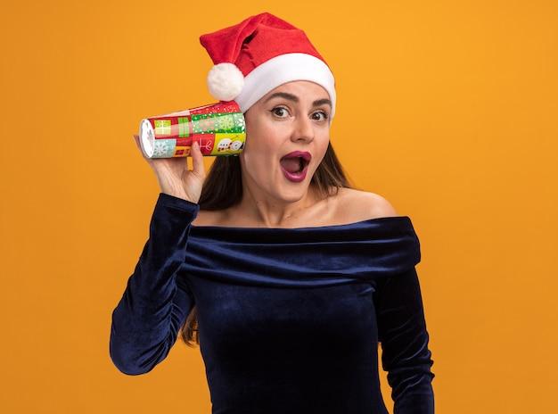 青いドレスとクリスマスの帽子を身に着けている興奮した若い美しい少女は、オレンジ色の背景に分離されたリスニングジェスチャーを示すクリスマスカップを保持しています