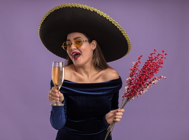 Excited young beautiful girl wearing blue dress and glasses with sombrero holding rowan branch with glass of champagne isolated on purple background