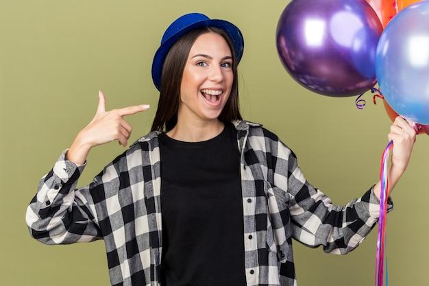 파란 모자를 쓰고 풍선을 가리키며 흥분한 아름다운 소녀