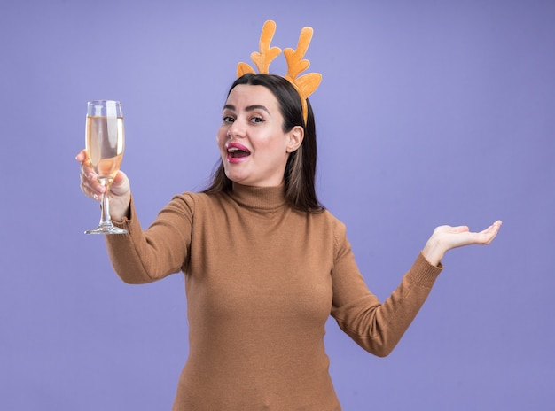 Excited young beautiful girl wearing brown sweater with christmas hair hoop holding glass of champagne spreading hand isolated on blue background