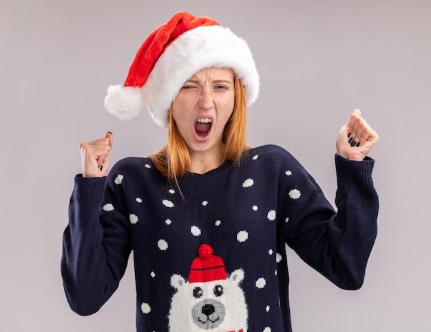 예 제스처를 보여주는 크리스마스 모자를 쓰고 흥분된 젊은 아름 다운 소녀 흰색 배경에 고립