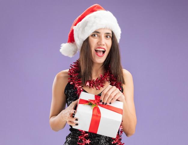 보라색 배경에 고립 된 선물 상자를 들고 목에 갈 랜드와 함께 크리스마스 모자를 쓰고 흥분된 젊은 아름 다운 소녀