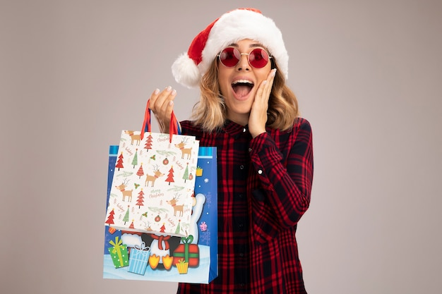 Eccitato giovane bella ragazza che indossa il cappello di natale con gli occhiali tenendo i sacchetti regalo mettendo la mano sulla guancia isolato su sfondo bianco