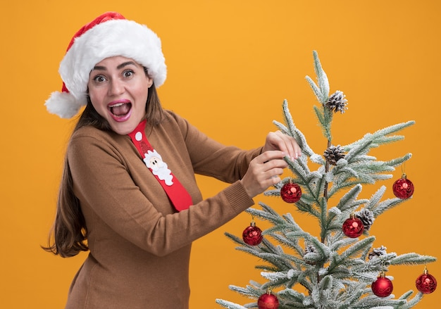 Excited young beautiful girl wearing christmas hat with tie standing nearby christmas tree isolated on orange background Free Photo