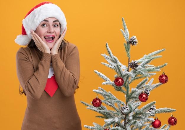 オレンジ色の背景で隔離の頬に手を置いてクリスマスツリーの近くに立っているネクタイとクリスマス帽子をかぶって興奮した若い美しい少女