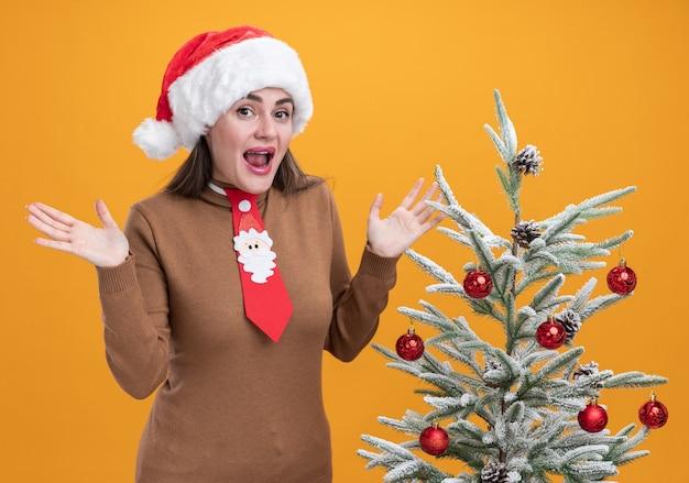 オレンジ色の背景で隔離の手を広げてクリスマスツリーの近くに立っているネクタイとクリスマス帽子をかぶって興奮した若い美しい少女