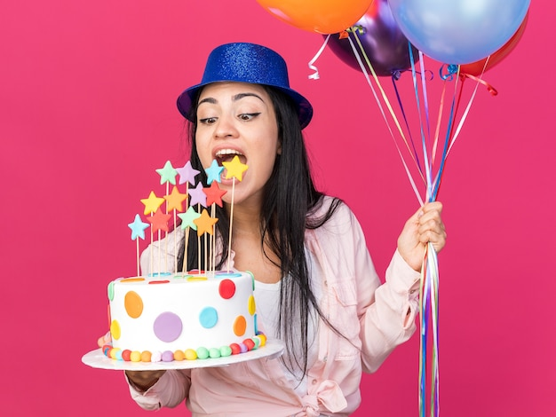 Excited young beautiful girl wearing party hat holding balloons with cake isolated on pink wall