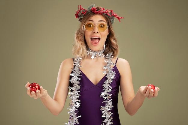 Возбужденная молодая красивая девушка в фиолетовом платье и очках с венком и гирляндой на шее держит елочные шары, изолированные на оливково-зеленом фоне